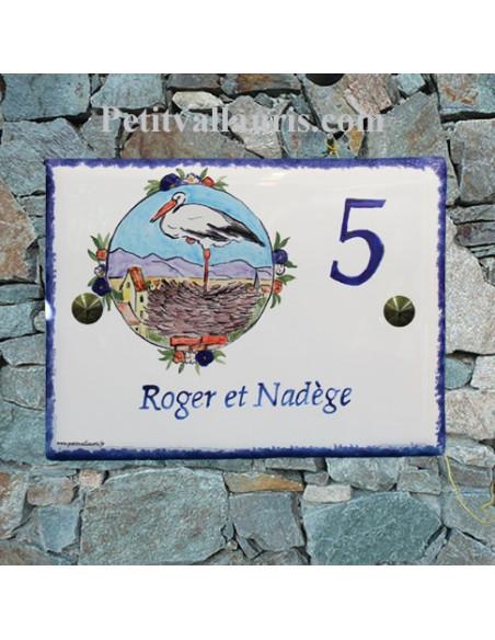 plaque pour maison en céramique émailléeée décor cigogne sur son nid en alsace inscription personnalisée couleur bleue